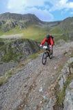 Mountain biker riding though Swiss mountain area Stock Photo