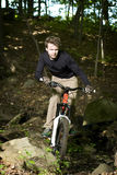 Mountain biker riding through trees Royalty Free Stock Images