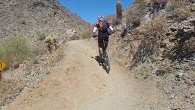Mountain biker riding uphill in the desert Royalty Free Stock Photos