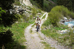 Mountain biker on rural road in mountain Stock Photo