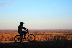 Mountain biker silhouette. Silhouette of the bicyclist standing on the bank of the river royalty free stock photo