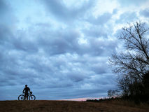 Mountain biker silhouette with clouds. Person standing next to bike on hilltop with dramatic clouds in background Royalty Free Stock Photography