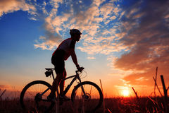 Mountain biker silhouette in sunrise. Silhouette of mountain biker against sunrise with clouds Royalty Free Stock Photography