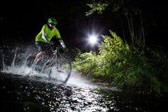 Mountain biker speeding through forest stream. Water splash in freeze motion. Royalty Free Stock Photos