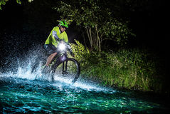 Mountain biker speeding through forest stream. Water splash in freeze motion. Royalty Free Stock Images