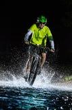 Mountain biker speeding through forest stream. Water splash in freeze motion. Stock Photo