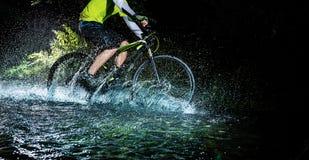 Mountain biker speeding through forest stream. Water splash in freeze motion. Stock Image
