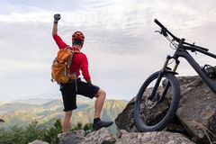Mountain biker success, looking at inspiring mountains. Mountain biker success, looking at view, bike trail in autumn mountains. Successful happy rider on top of Royalty Free Stock Photo
