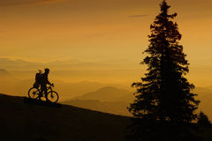 Mountain biker at sunset. Mountain bikers silhouette against beautiful sunset landscape