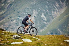 Mountain biker on trails. Mountain bike cyclist in sport equipment and helmet riding on rugged trails Royalty Free Stock Photography