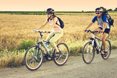 Mountain bikers. Active male and girl  mountain bikers riding bicycle in nature Royalty Free Stock Photo