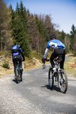 Mountain bikers going uphill. Mountain bikers riding on bikes to the top of the hill Royalty Free Stock Photo