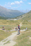 Mountain bikers riding though Swiss mountain area Royalty Free Stock Images