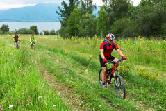 Mountain bikers on road beside lake stock photos