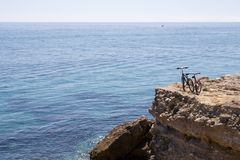 Mountain Bikes and Sea. A pair of mountain bikes parked on a cliff overlooking the sea stock photo