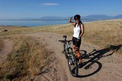 Mountain biking. Smiling female mountain biker enjoying the view Stock Photo