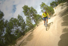Mountain Biking. Rider riding bike on dirt track Stock Photos