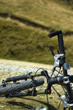 Mountain biking. Bicycle detail with mountain in background royalty free stock image