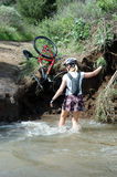 This is mountain biking. Bike hanging with women in water stock photography