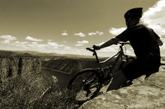 Mountain biking. Mountain biker taking a rest at the top of Flaming Gorge rim, UT Royalty Free Stock Photography