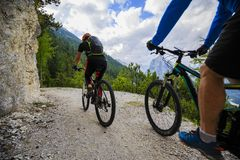 Mountain biking couple with bikes on track, Cortina d`Ampezzo, D Stock Image
