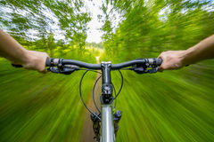 Mountain biking down hill descending fast on bicycle. Royalty Free Stock Photography