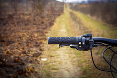Mountain biking down hill descending fast on. Bicycle. View from bikers eyes Royalty Free Stock Photography