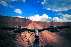 Mountain biking down hill descending fast on. Bicycle. View from bikers eyes Royalty Free Stock Photos