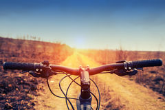 Mountain biking down hill descending fast on. Bicycle. View from bikers eyes Stock Photo