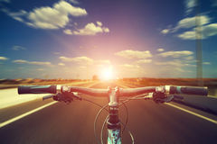 Mountain biking down hill descending fast on bicycle. View from. Bikers eyes Royalty Free Stock Photography