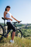 Mountain biking happy sportive girl relax in meadows sunny countryside Stock Image