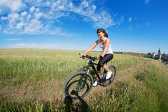Mountain biking happy sportive girl relax in meadows sunny countryside Stock Images