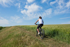 Mountain biking happy sportive girl relax in meadows sunny countryside Royalty Free Stock Photos