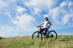 Mountain biking happy sportive girl relax in meadows sunny countryside Stock Photo