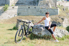 Mountain biking happy sportive girl relax in meadows sunny countryside Stock Photography
