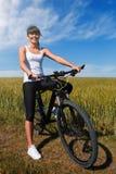 Mountain biking happy sportive girl relax in meadows sunny countryside Stock Photos