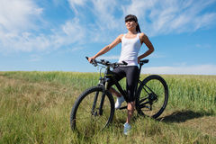 Mountain biking happy sportive girl relax in meadows sunny countryside Royalty Free Stock Image