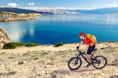 Mountain biking at the seaside bike dirt enduro trail. Mountain biker riding on bike in summer inspirational mountains and sea landscape. Man cycling MTB on stock photography