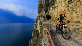 Mountain biking at sunrise woman over Lake Garda on path Sentier Royalty Free Stock Photos