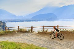 Mountain biking at sunrise woman over Lake Garda on path Sentier Stock Photography