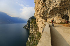 Mountain biking at sunrise woman over Lake Garda on path Sentier Stock Photos