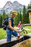 Mountain biking woman drinking water. stock images