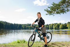 Mountain biking young woman relax by lake Royalty Free Stock Images