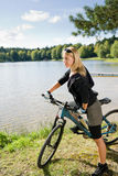 Mountain biking young woman relax by lake Royalty Free Stock Photo