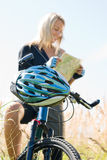Mountain biking young woman search in map Royalty Free Stock Photos