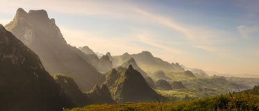 Mountain and blue sky at Kasi, Laos. And little home in grass field in front of mountain royalty free stock photo