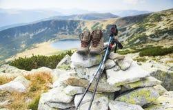 Mountain boots and trekking sticks on mountain peak Stock Photo
