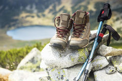 Mountain boots and trekking sticks on mountain peak Stock Photos