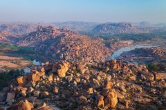 Hampi Vijayanagara Empire monuments, India. Mountain with boulders and river at Hampi, the centre of the Hindu Vijayanagara Empire in Karnataka state in India stock images