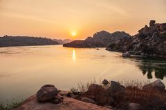Mountain with boulders in Hampi. Mountain with boulders and river at Hampi, the centre of the Hindu Vijayanagara Empire in Karnataka state in India royalty free stock image